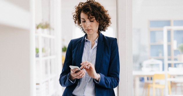 Woman standing in door frame of office using mobile device.