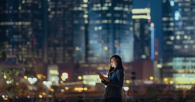 Woman using tablet at night in a big city.
