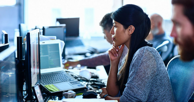 Woman looking at multiple screens with code; trying to problem-solve.