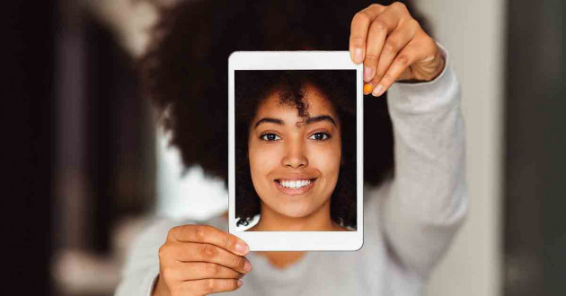 Woman holding iPad infront of her that shows her face.