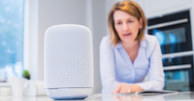 Woman using a smart IoT device in her home: IoT security